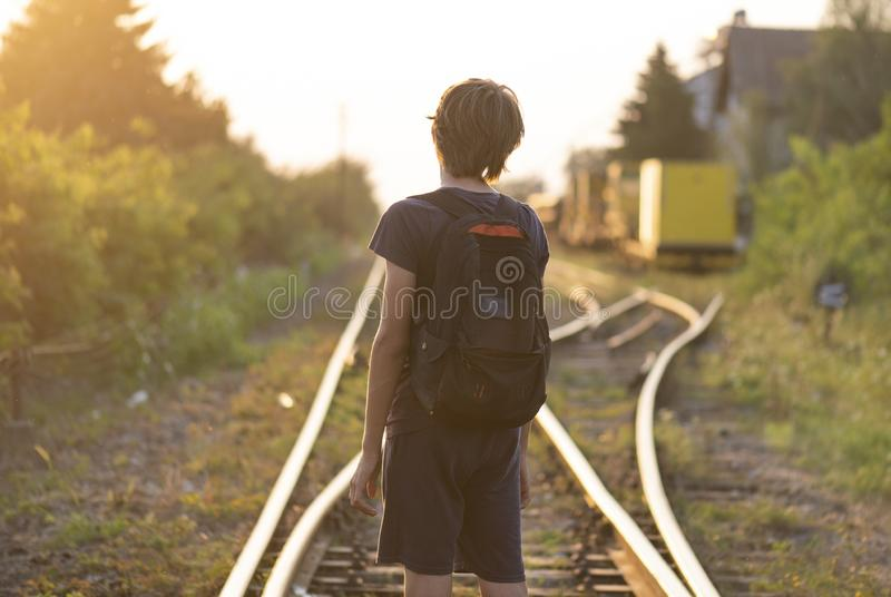 A lonely boy with a bag stand on the rails stock images