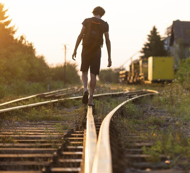 A lonely boy with a bag is walking on the rails stock images