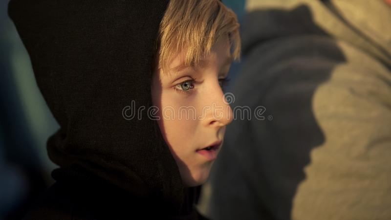 Lonely boy in hoodie sitting outdoor, bullying victim, humiliation at school royalty free stock photos