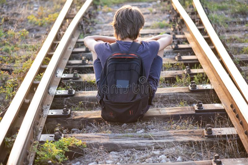 A lonely boy sitts on the rails stock image