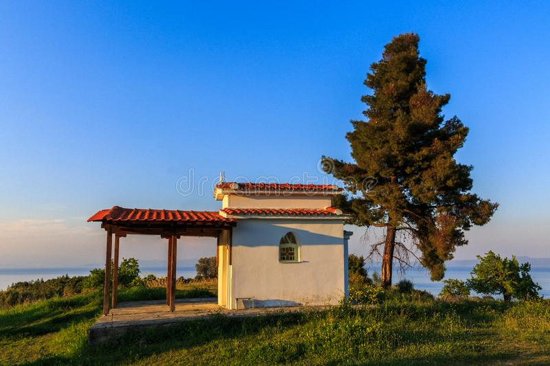 A lonely chapel under a tree on the hill of the sea coast in a c. Oastal Greek village at dawn of the day, Kassandra