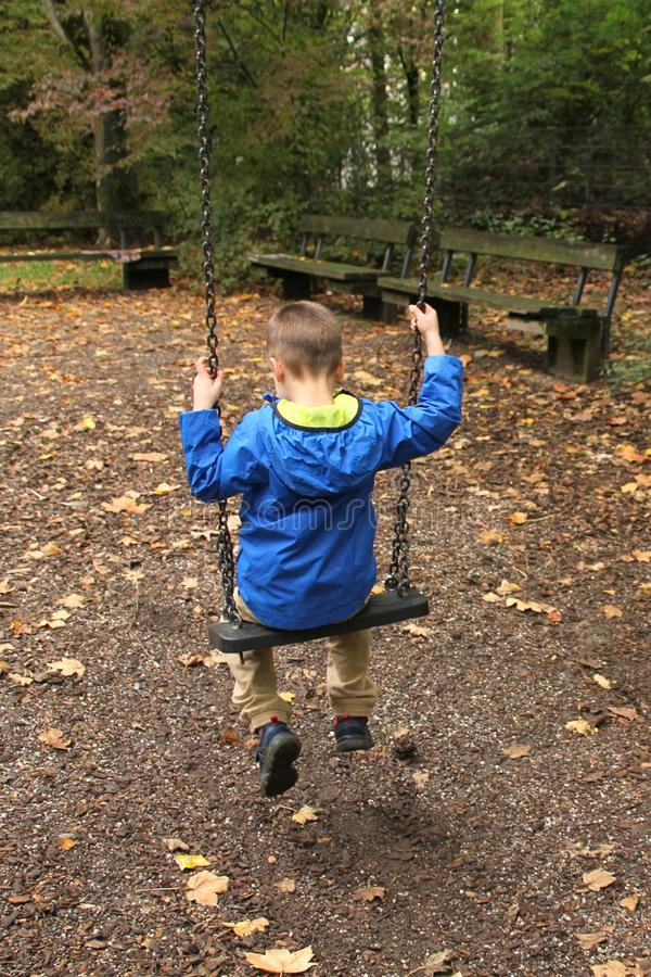 Free Lonely Child In A Blue Jacket Sits On A Swing In A Park In An Autumn Park, The Concept Of Loneliness Stock Images - 160846564