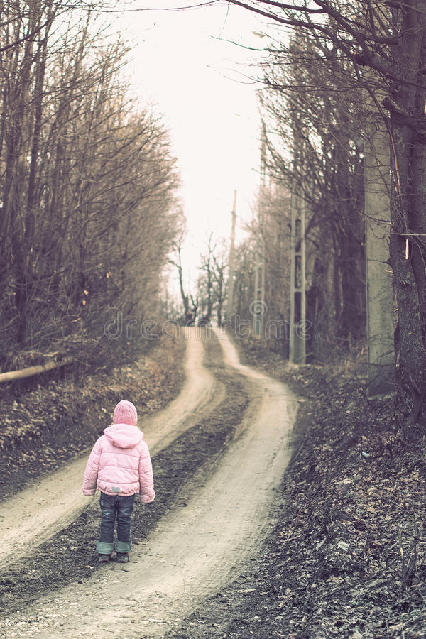 Lonely children on a forest road. Lonely little girl pink dressed walking on a forest road stock photos