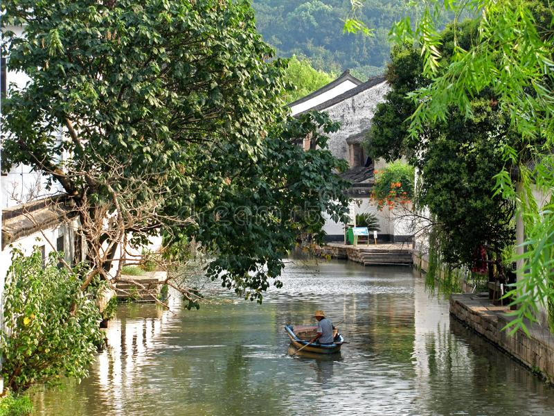 A Chinese old man rowing in a small boat along a wide water channel in Shaoxing China royalty free stock photography