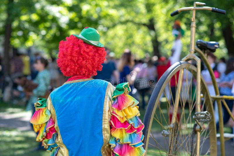 Lonely clown in colorful costume in front of people. In the park royalty free stock image