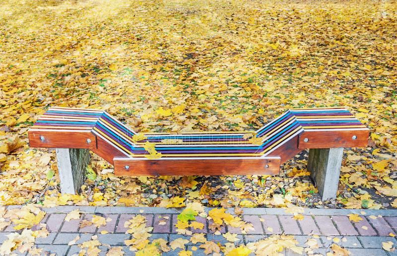 Lonely colorful wooden bench in park in the autumn stock photography