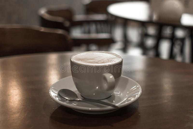 Lonely cup of coffee on the table in a cafe. A cup of coffee, espresso or latte. Coffee break. Hot morning drink. Meeting at a coffee shop or cafe. White cup and stock image