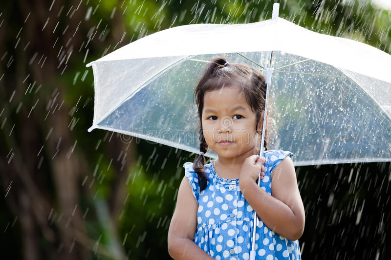 Lonely cute asian little girl with umbrella in rain. Portrait of lonely cute asian little girl with umbrella in rain royalty free stock photos