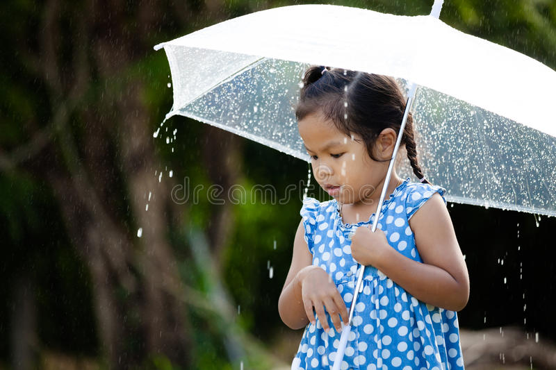 Lonely cute asian little girl with umbrella in rain. Portrait of lonely cute asian little girl with umbrella in rain stock images