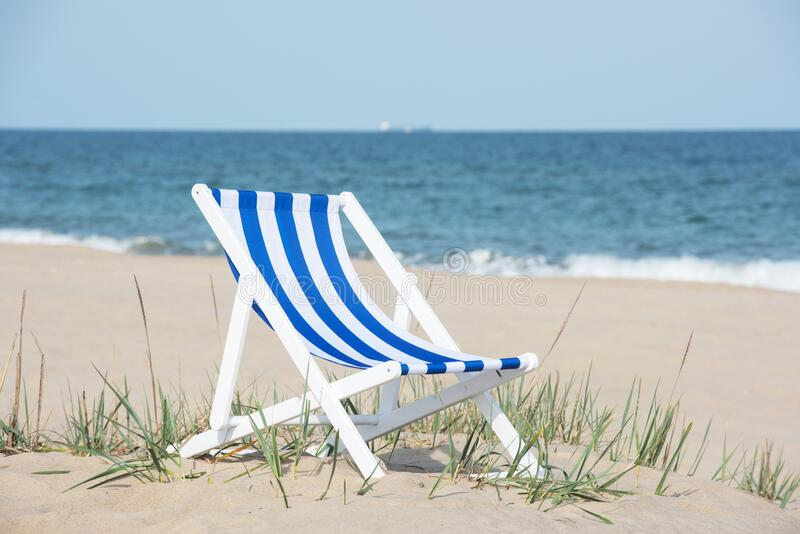 Lonely deck stripped chair on the empty beach stock photo