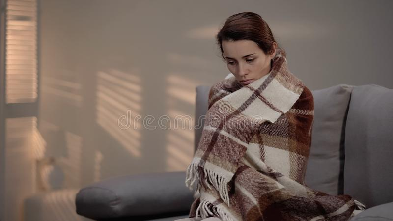 Lonely depressed female sitting on couch, covered with plaid, unemployment royalty free stock photos