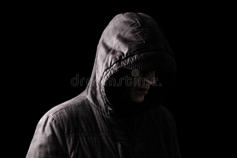 Lonely, depressed and fragile Caucasian or white man hiding face, standing in the darkness stock image