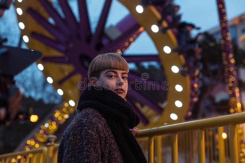 Lonely depressed girl walking into amusement park. Lonely girl walking into amusement park. Problem of sexual minorities, depression royalty free stock images