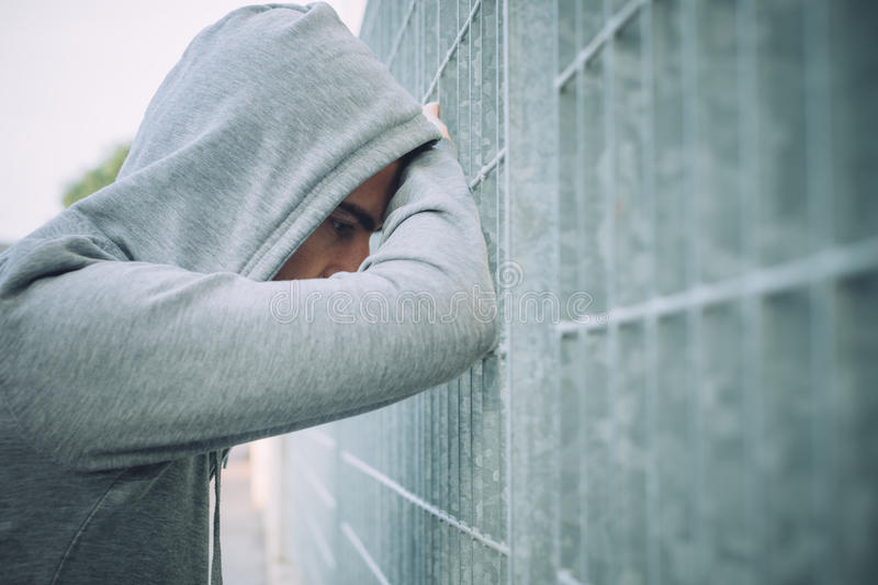 Lonely and depressed Man Leaning against a Fence stock photos