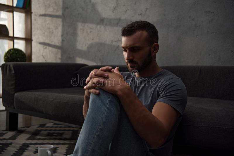 Lonely depressed man sitting. At home stock images