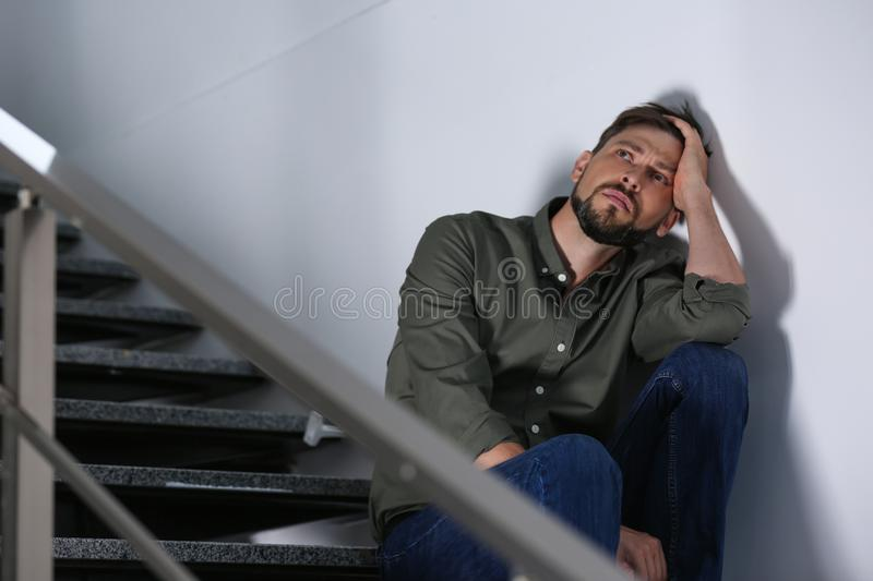 Lonely depressed man sitting on stairs royalty free stock image