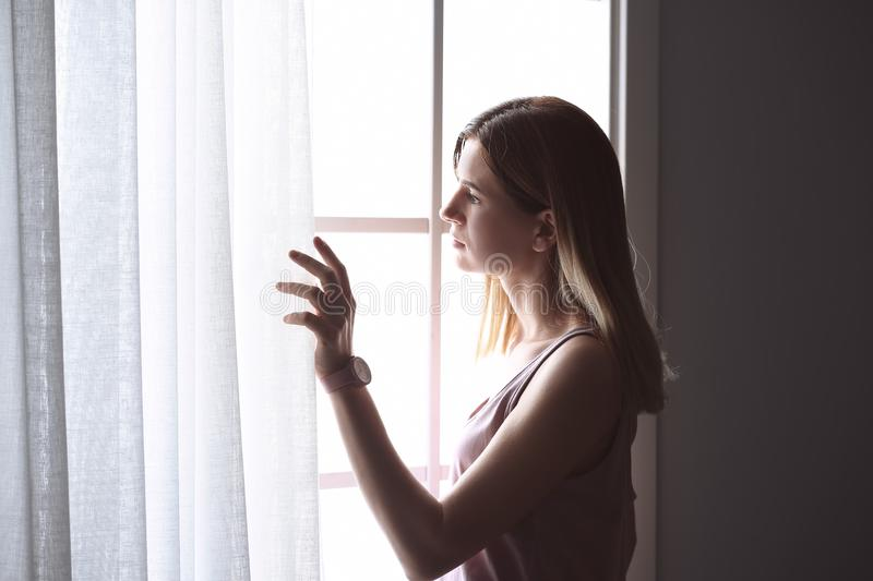 Lonely depressed woman near window stock photography