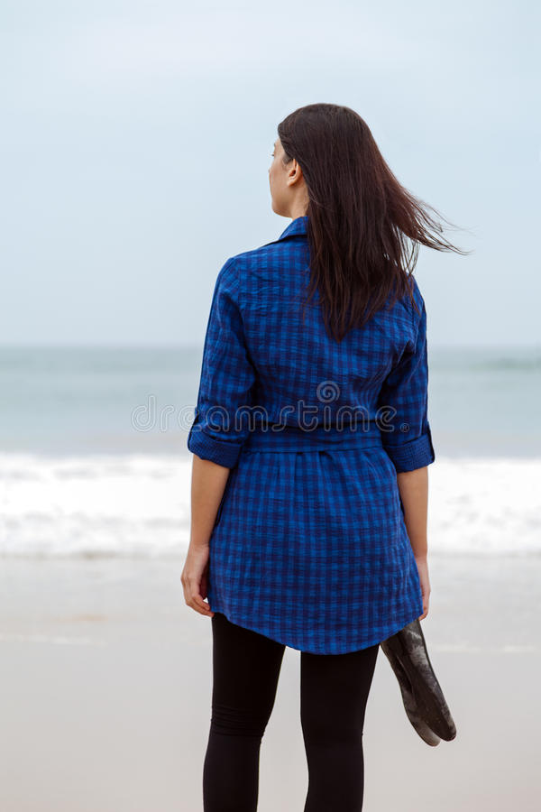 Lonely and depressed woman standing in front of the sea. In a deserted beach on an Autumn day royalty free stock photos