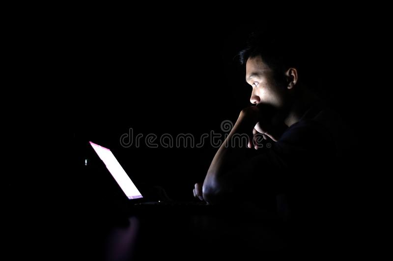 Lonely developer thinking solution with laptop at night in dark room stock photo