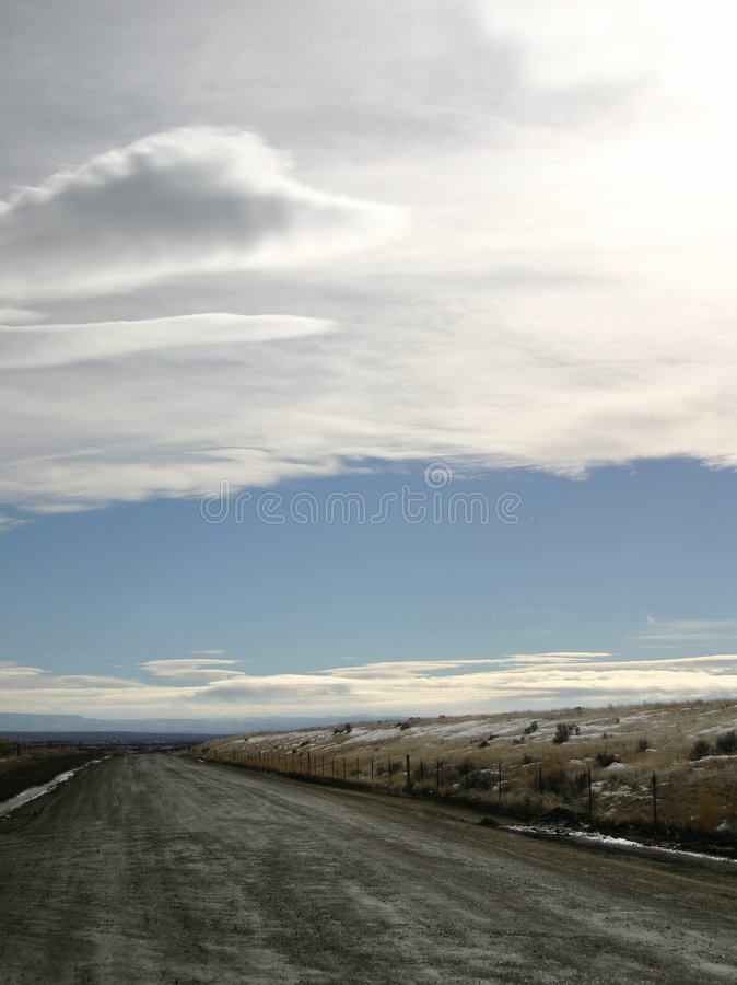 Lonely Dirt Road. A lonely dirt road leads to nowhere or somewhere. Some snow on the ground. Great for travel, destinations, road trips,escape and more. Room for stock image