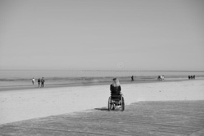 Lonely disabled young woman on beach. Sunny summer day stock image