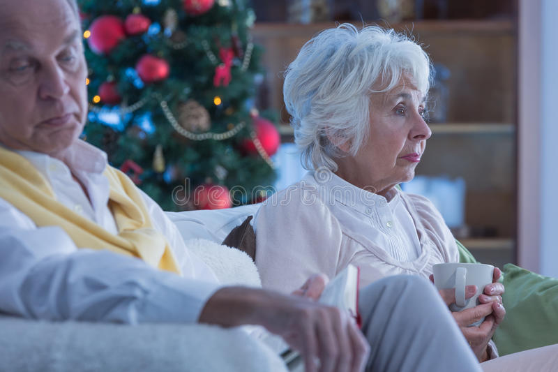 Lonely elderly couple. Sitting on a sofa during Christmas stock image