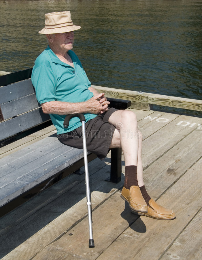Lonely elderly man. Old man with cane sitting on bench royalty free stock images