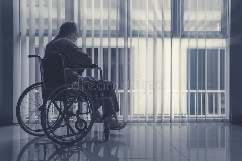 Lonely elderly man sitting on wheelchair. Near the window at home stock photos