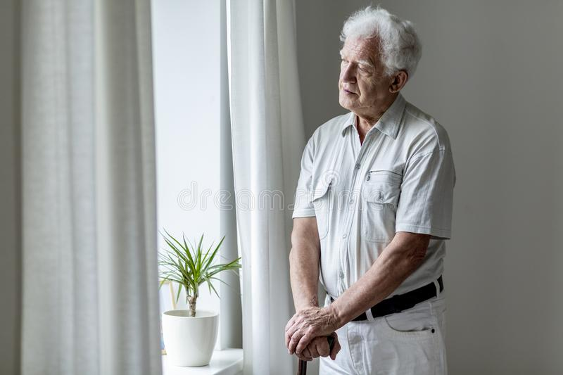 Lonely elderly man with walking stick standing by the window alo stock image