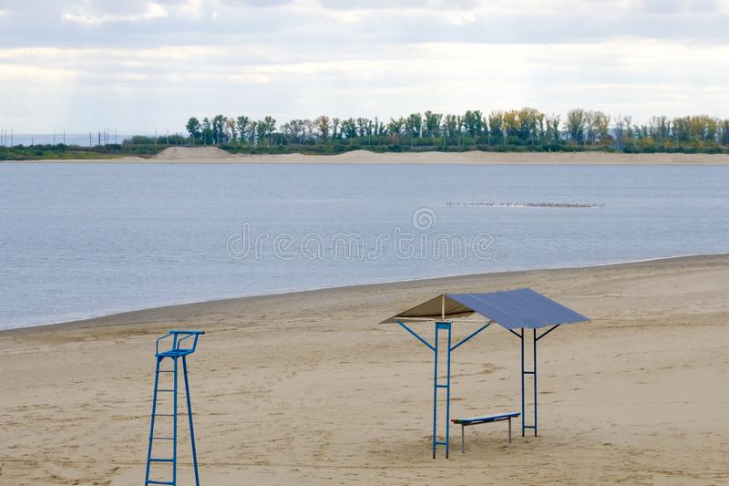 Lonely empty beach shore within the city. On the background of the beach buildings. Tower and gazebo stock images