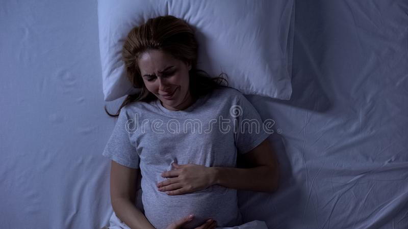 Lonely expecting woman crying in bed, holding belly, hopelessness and depression stock photo