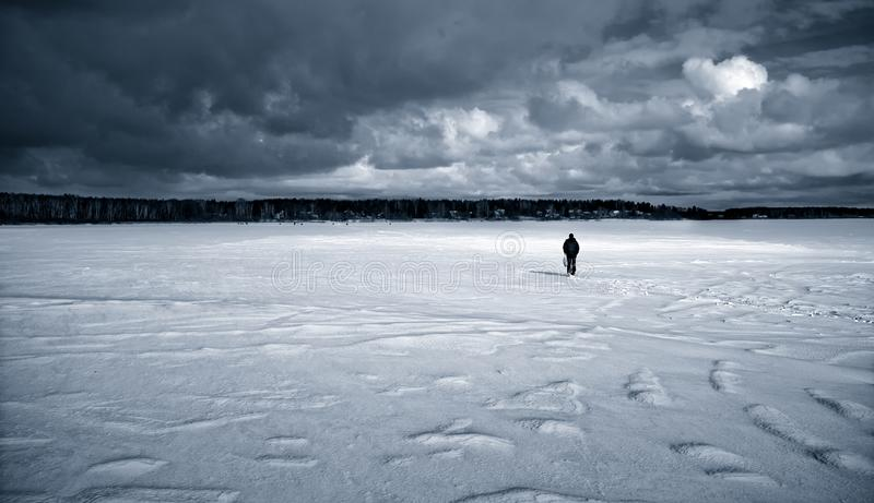 A lonely figure in a snow-covered frozen lake. royalty free stock images