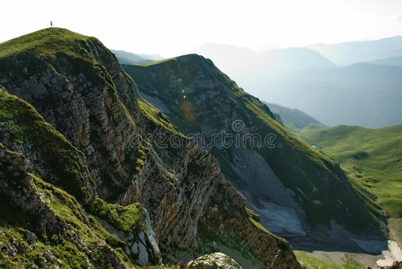 Lonely figure on the top of the mountain. Silhouette of a man on the edge of the cliff. Summer vibes. Trekking in the mountains stock photo