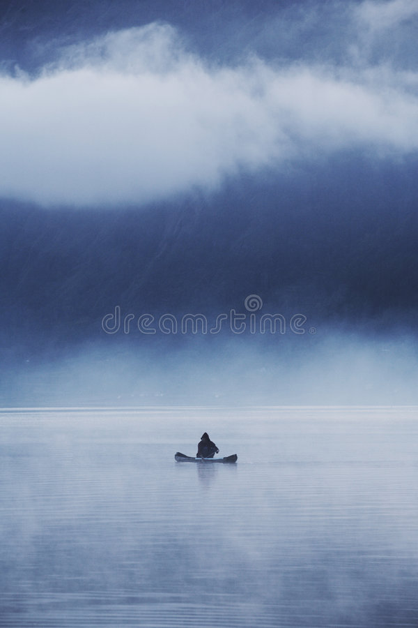 Lonely Fisherman. Fisherman with his small boat in a misty morning