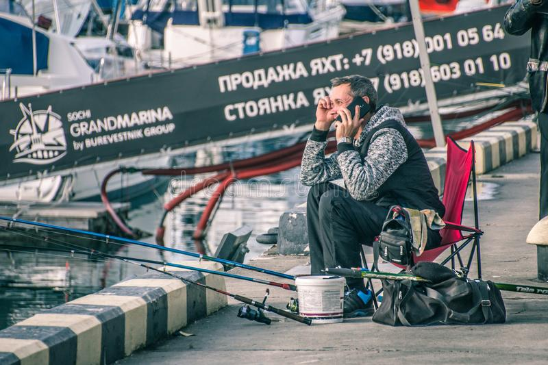 Lonely fisherman on the background of the black sea. Yachts. Sochi sea port. street fishermen. pier. Central embankment of Sochi stock images