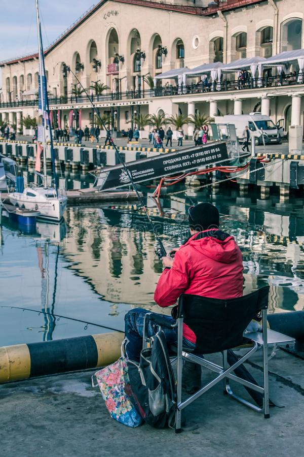 Lonely fisherman on the background of the black sea yachts. Sochi sea port. street fishermen. pier. Central embankment of Sochi royalty free stock photo