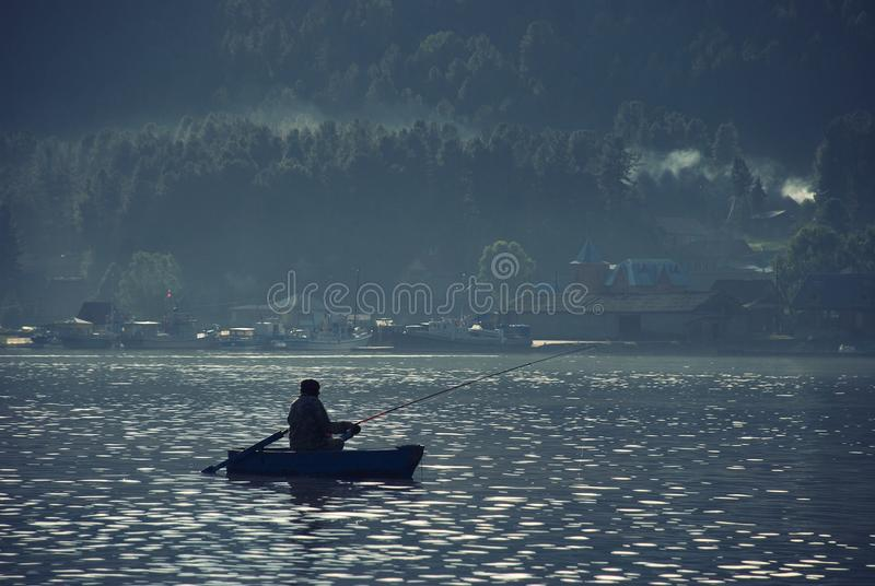 One male fisherman in a wooden boat fishing on the lake late at night. On the shore of the village and high mountain and green for stock images