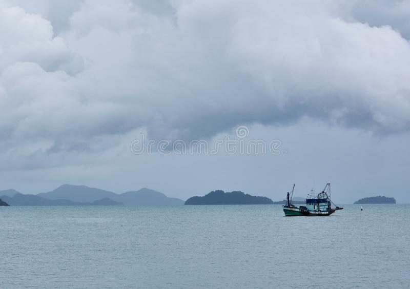 Lonely fishing boat at anchor on bay with mountain background royalty free stock photo