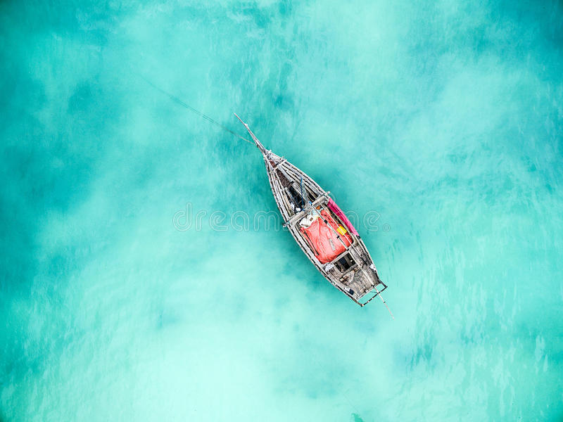 Lonely fishing boat in clean turquoise ocean, aerial photo. Top view royalty free stock photos