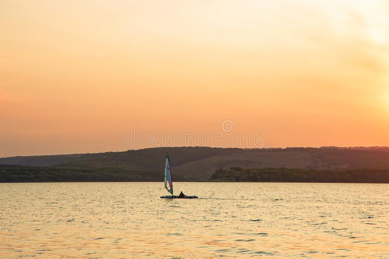 Lonely fishing boat on lake peaceful waters calm valley scenery landscape view in evening sunset lighting orange sky background,. Lonely fishing boat on lake stock photography