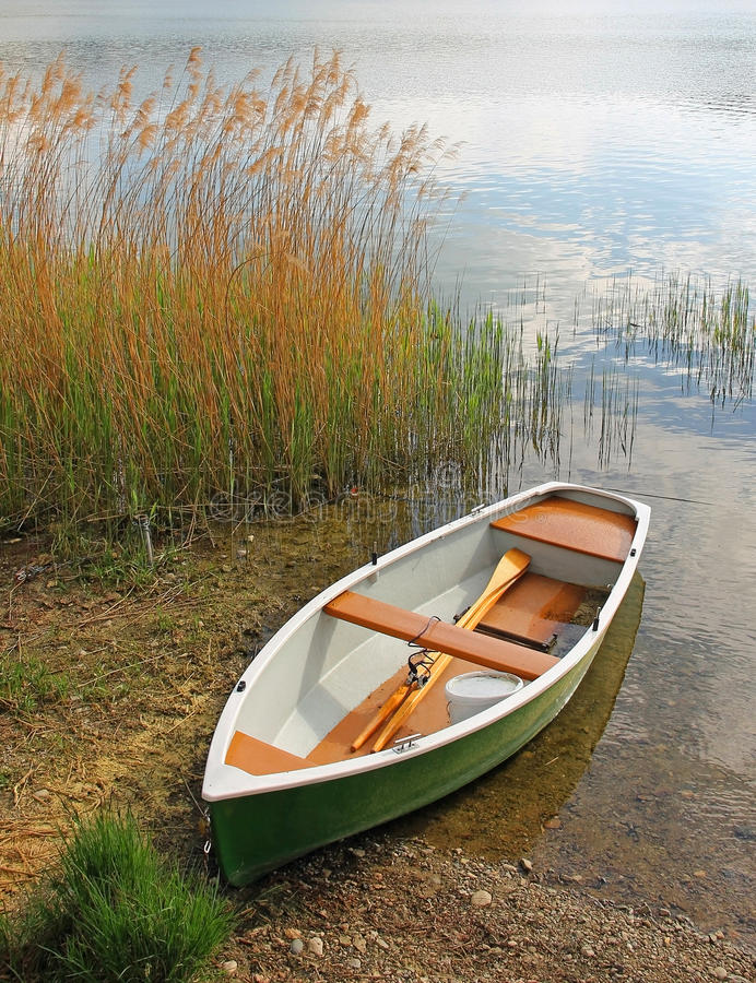 Lonely fishing boat at the lakeside. In autumn stock photos