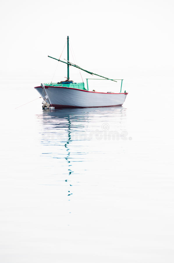 Lonely fishing boat on very calm sea stock image