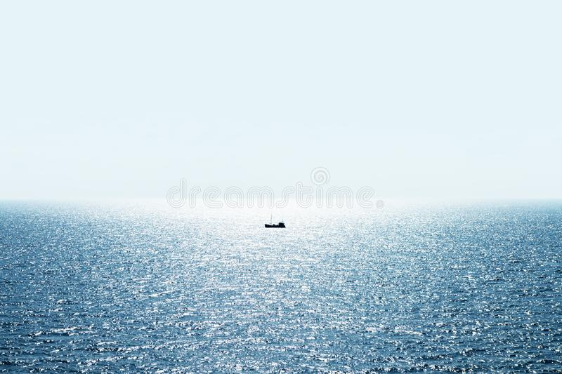 Lonely fishing ship trawler boat on ocean royalty free stock photo