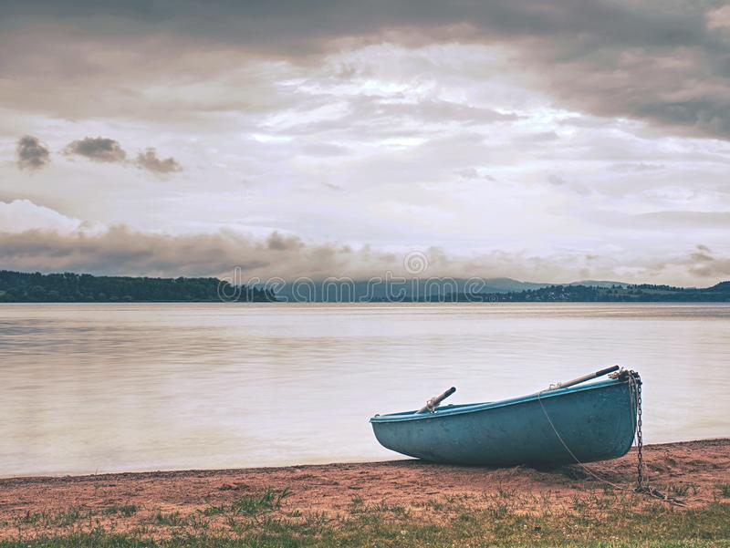 Lonely fishing vessel boat docked on beach at calm lake. Laminate or wooden fishing boat in a still lake water, vacation, travel, summer, smooth, level, small royalty free stock images