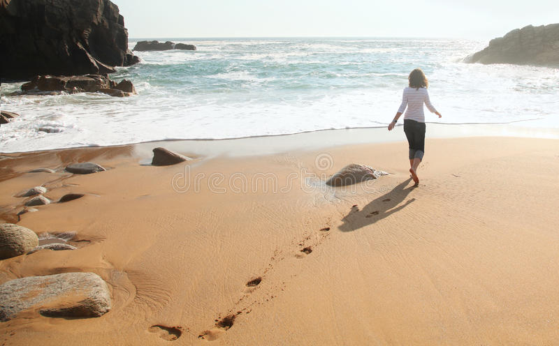 Lonely girl at the beach stock photography