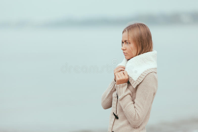 Lonely girl on the beach. Attractive lonely and sad girl on the beach stock image