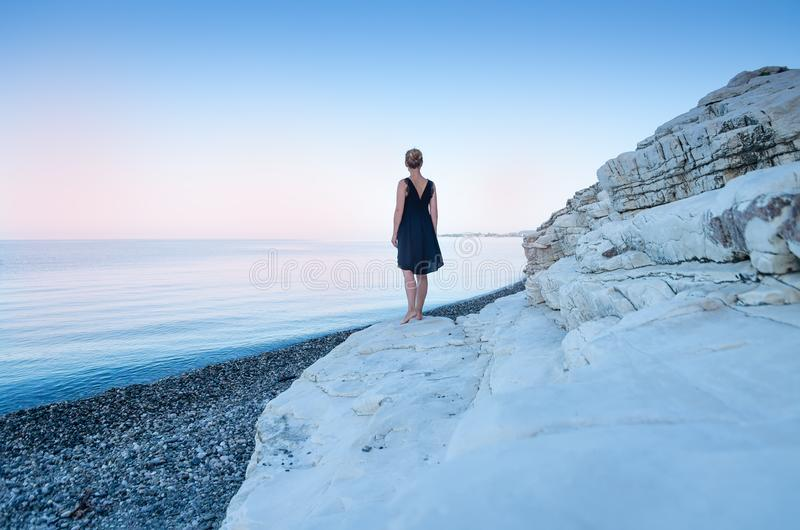 A lonely girl in a black dress stands on the seashore. White rocks. The concept of minimalism stock photos