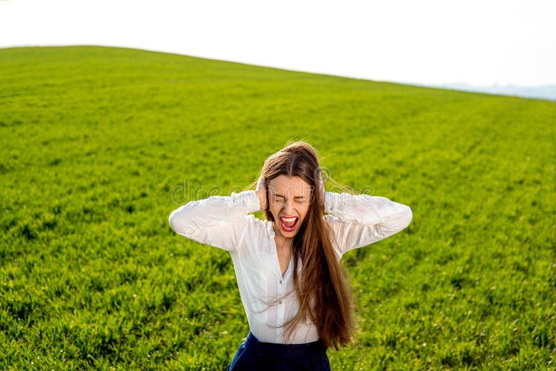 Lonely girl crying in the green field with sky royalty free stock image