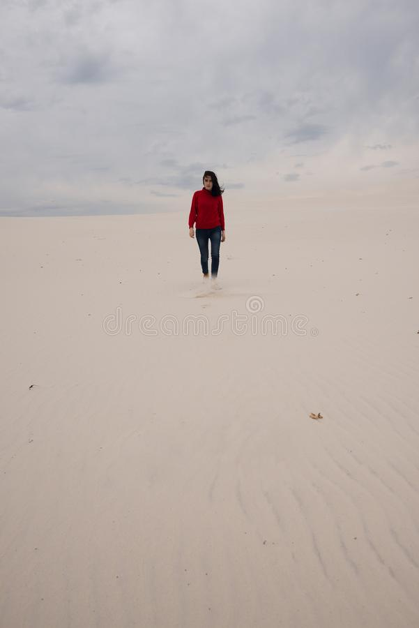 Lonely girl, with flying hair, goes through the desert. On the background of gray sky stock photography
