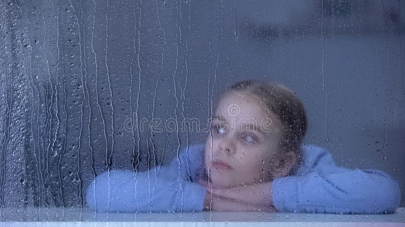 Lonely girl looking through rainy window lack of parental love and care, boredom stock photos